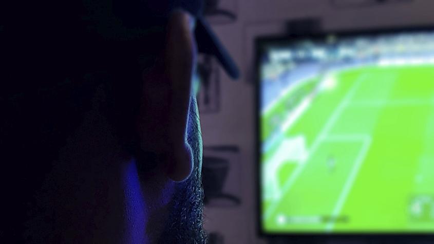 Man die voetbal op televisie kijkt