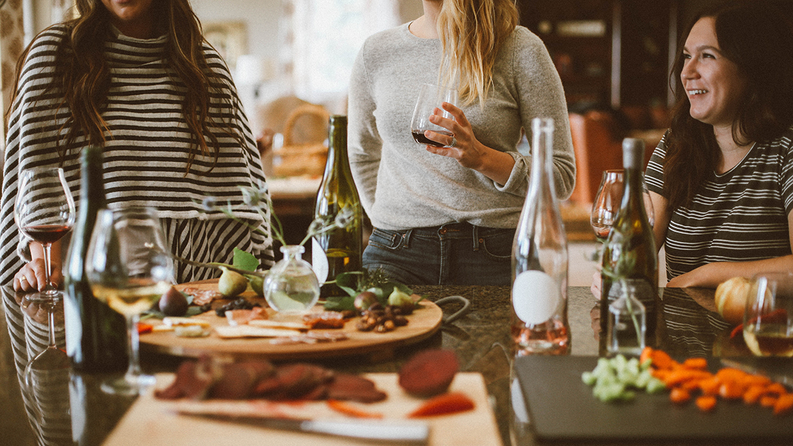 Drie vrouwen met wijn en eten