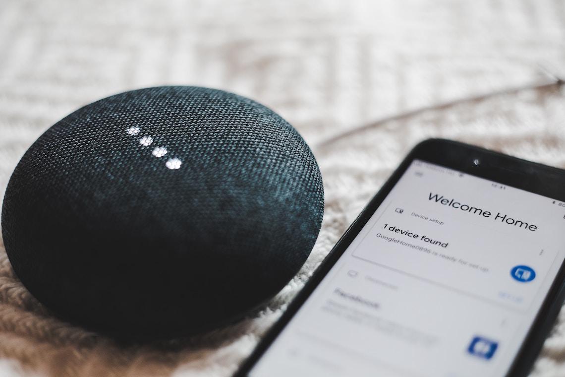 Google Home Device met mobiele telefoon ernaast